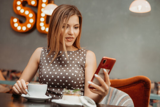 Beautiful relaxed woman using a mobile phone in cafe. Reading news or SMS