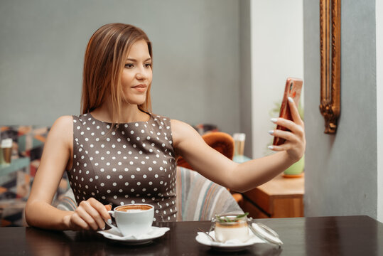 Beautiful relaxed woman using a mobile phone in cafe. Making selfie