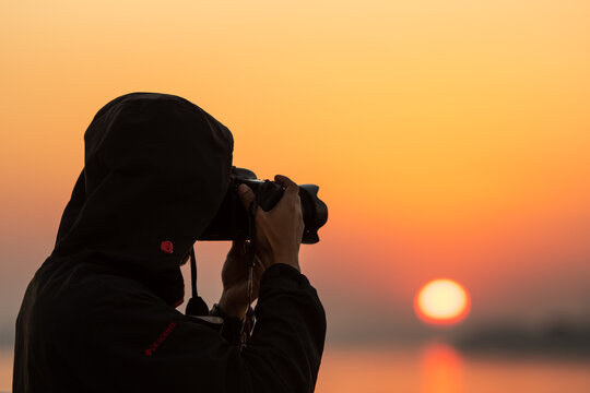 Photographer tourists taking pictures during sunset Silhouette  time.