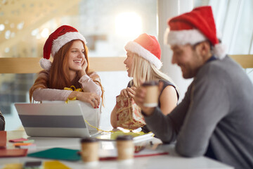 young people , employees, enjoying christmastime in bright office with santa hats