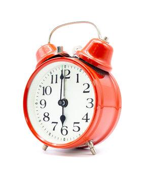 Roter Wecker zeigt sechs Uhr vor weißem Hintergrund