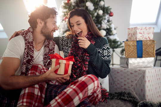 A young couple sitting on the floor surrounded by Xmas presents. Christmas, relationship, love, together