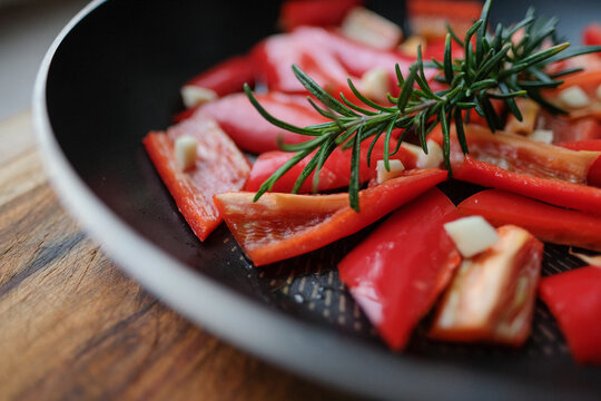 Mediterrane Küche, Paprika und Rosmarin in einer Pfanne mit Knoblauch