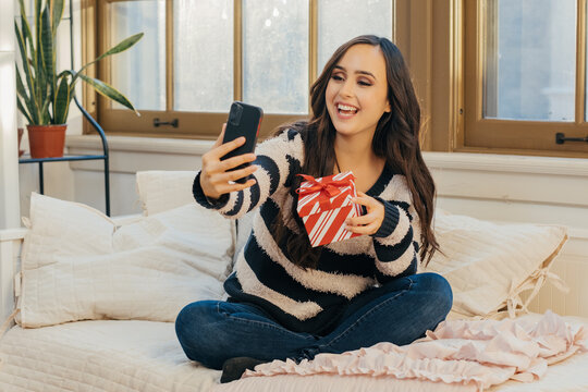 Portrait of a smiling young woman celebrating with Christmas gift over the phone at home