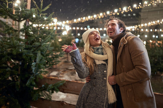 A young couple in love excited about snowfall in the city. Christmas tree, love, relationship, Xmas, snow