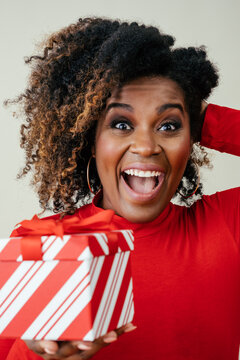 Portrait of a very excited woman holding red Christmas gift box with mouth open