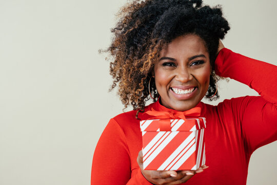Portrait of a happy mid woman smiling and holding red Christmas gift box