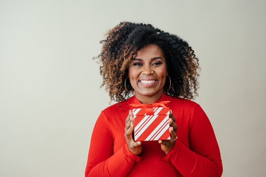 Portrait of a very happy mid woman smiling and holding red Christmas gift box