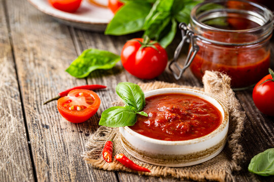 Bowl of italian tomato sauce with basil and fresh tomatoes on wooden background