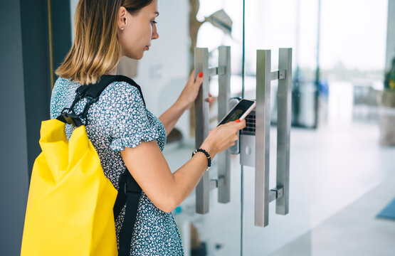 Focused woman using smartphone for opening door
