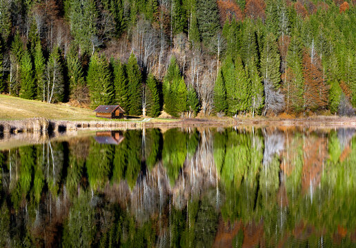 Beautiful single wooden hut surrounded by autumn trees reflected in mountain lake