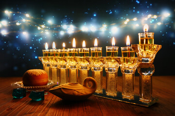 image of jewish holiday Hanukkah background with crystal menorah (traditional candelabra) and oil...