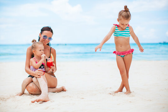 Adorable little girls and young mother on tropical white beach