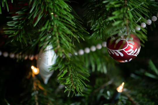 Decorated Christmas tree, real Nordmann fir in front of blurred background. Macro photography shows 2 Christmas balls in red and white and a white pearl necklace