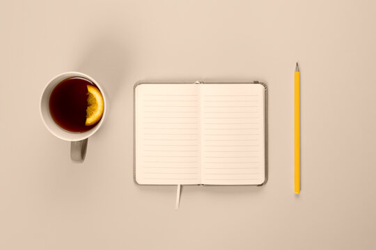 Tea cup and fancy notebook with empty or blank page on desk from above. Mock up toned in trendy 2021 color.