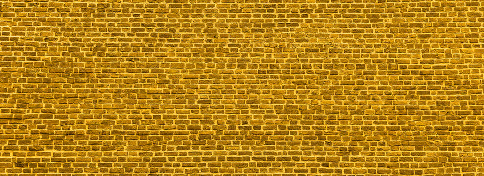 Brick wall, wide panorama of golden color masonry. Wall with small Bricks. Banner toned in trendy 2021 color.