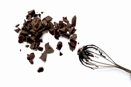 Broken Chocolates And Wire Whisk On White Background