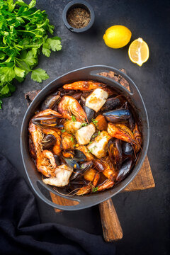 Traditional French seafood bouillabaisse with fish, king prawns and mussels in tomato sauce as top view on a modern design plate