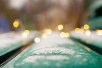 Snow covered street bench and bokeh of yellow garland in new year season Fotomurales
