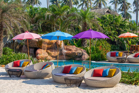 Umbrella and chair around swimming pool in tropical resort.