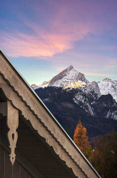 Beautiful view of first sunlight on Alpsitze mountain with artistic wooden roof  in foreground