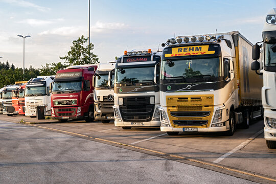 Row of various Volvo, Mercedes and DAF  trucks parked at a truck overnight parking.