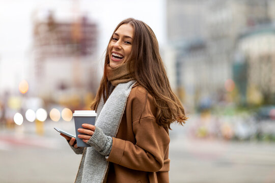 Smiling young woman with smart phone and coffee cup outdoors at urban setting