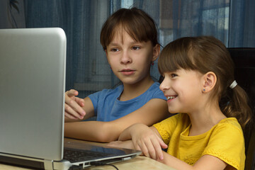 Two girls looking at the laptop and smile. Concept of home distance learning.