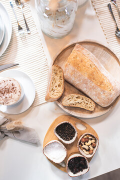 Ciabatta auf einem Holzteller mit Kaffee und Gewürzen