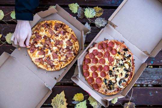 Dos pizzas en su caja de cartón sobre una mesa de madera con hojas caídas en otoño