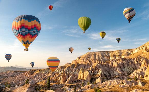 Hot air balloons flying in sunset sky Cappadocia, Goreme, Turkey. Great tourist attraction - sunrise balloning over Cappadocia valleys
