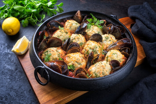 Traditional Norwegian fish ball fiskeboller with fish and mussels in red wine sauce as close-up in a modern design pot