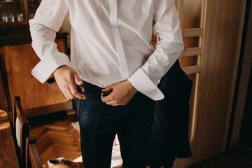 Fototapeta Pan młody zakłada skórzany pasek lub dominacja mężczyzny w garniturze