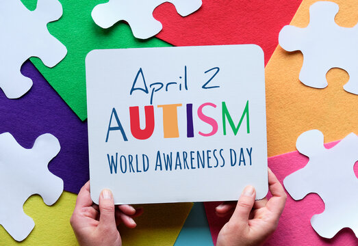 Hands hold board. with text April 2 Autism World Awareness day. Puzzle, layered felt background.