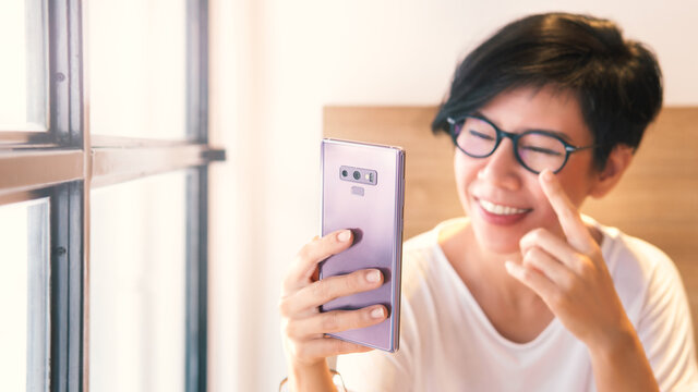 Beautiful middle aged Asian woman smile, talk and online video call with family and friends with smartphone at home during pandemic of Covid-19. New normal, social distancing & stay home concept