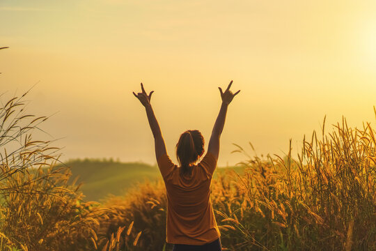 Asian woman standing and hand up and show i love you hand gesture sign in tropical forest and looking far away at sunrise time.