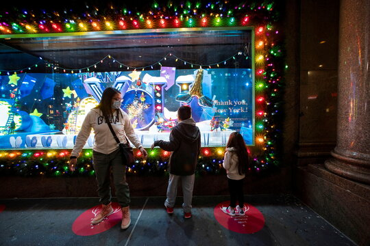 People watch a Christmas window of the Macy's Herald Square store in New York City, New York