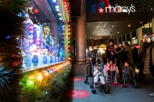 People watch Christmas window of the Macy's Herald Square store in New York City, New York