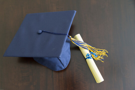 Close-up Of Mortarboard With Certificate On Table