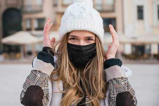 Portrait of a beautiful young woman wearing face mask and winter clothes