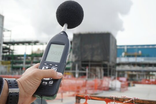 Hand of Environmental officer holding to use sound level meter for monitor is part of the prevention of environmental impacts at Chemical plant area or refinery factory.