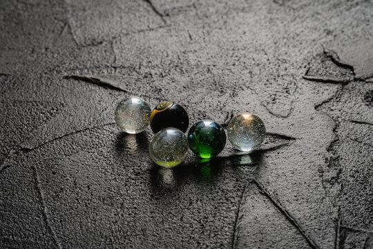 bolas de vidrio cristal transparente negra ay verde sobre base de cemento cordoba argentina