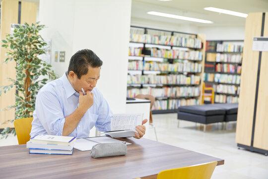 図書館で調べ物する男性