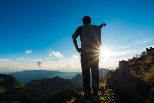 Photographer man standing on ledge of a mountain enjoying the beautiful sunset against blue sky cloud