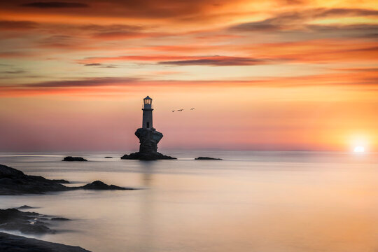 Romantic sunrise behind the famous Tourlitis lighthouse situated on a steep rock in the sea at the cycladic island of  Andros, Greece