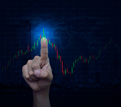 Hand pressing to trading graph of stock market over world map, modern city tower and skyscraper, Business investment concept, Elements of this image furnished by NASA