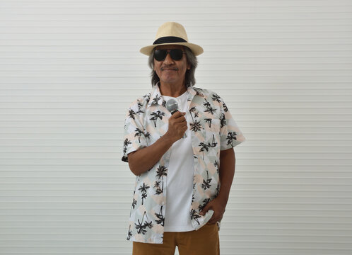 Happy senior traveler asian man wearing straw hat, sunglasses and summer shirt singing with microphone standing over white wall background, Business summer holiday concept