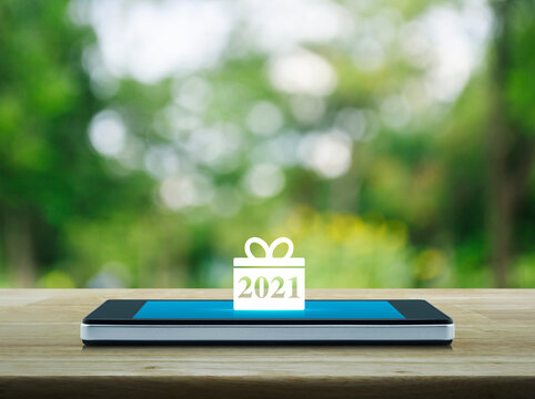 Gift box happy new year 2021 flat icon on modern smart mobile phone screen on wooden table over blur green tree in park, Business happy new year 2021 shop online concept