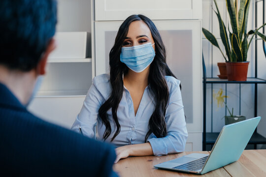 Portrait of a business woman at meeting sitting at desk with customer wearing face mask for social distancing due to coronavirus