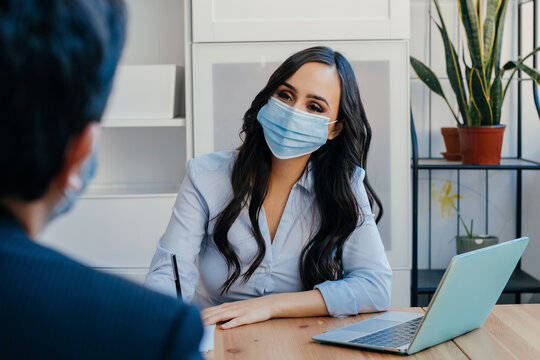 Portrait of a business woman at meeting sitting at desk with client wearing face mask for social distancing due to coronavirus